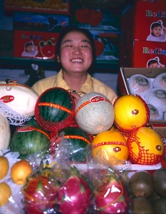 Happy melon seller Urumqi.  I was particularly fascinated by the similarity between the shape of the melons and the seller's face.