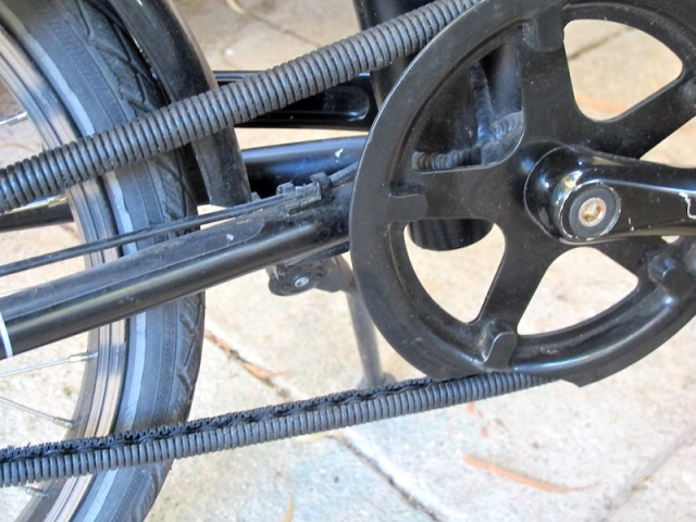 The split electrical conduit chain guard. The piece missing from the sprocket guard is a result of airline baggage handlers' irreverence to bicycles.