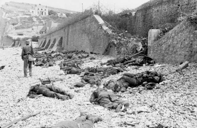 Dead Canadian soldiers lie where they fell trapped between the sea and the fortified sea wall. German machine gun slits can be seen in the bunker above the standing soldier's head. Image credit: German archives.