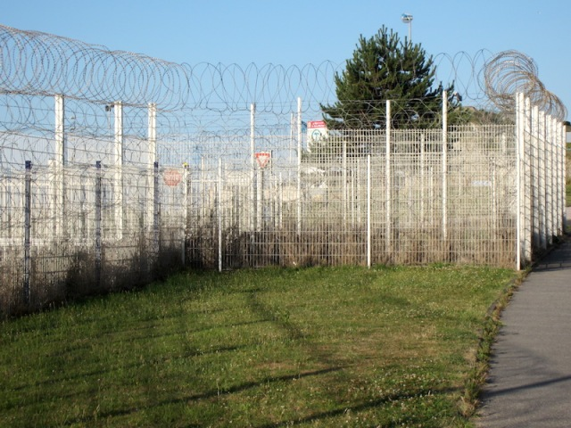 A concertina razor wire fence along the edge of the bike track to the ferry terminal, obviously erected to deter refugees seeking asylum in England.