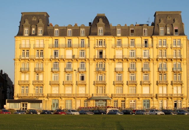 A majestic building with a fine example of a mansard roof opposite the beachfront.