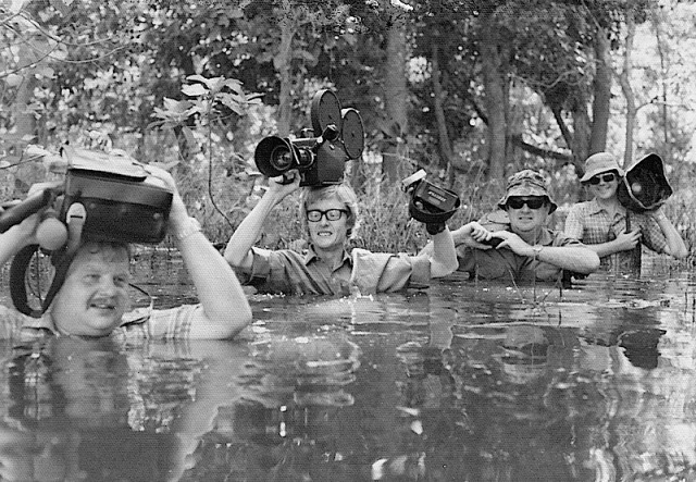 Ted with camera on his head wading across a creek in New Guinea.