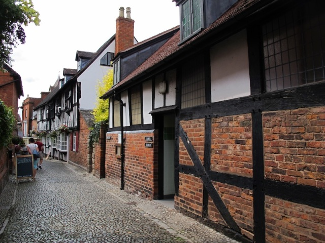 A street of box-framed houses with terracotta brick infill.